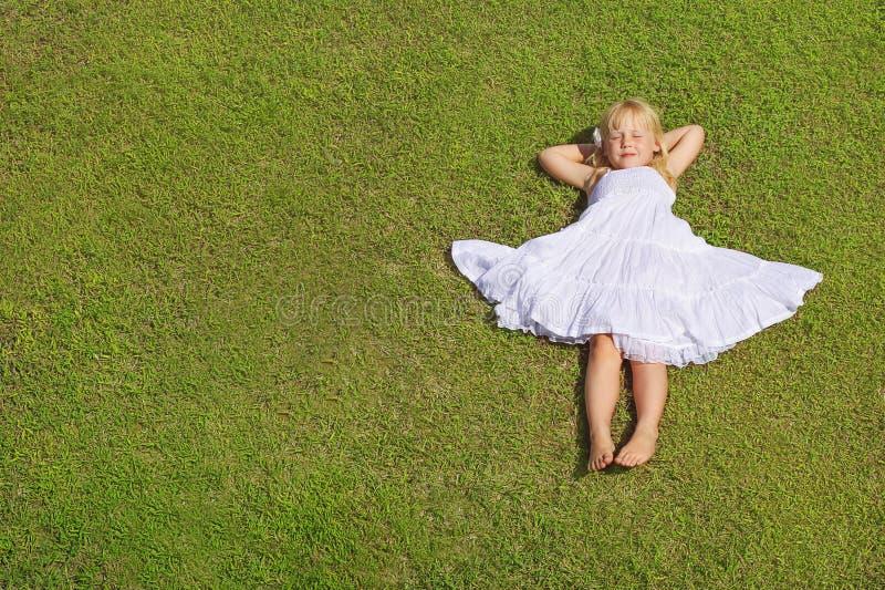 Muchacha que miente en la hierba verde, visión superior del niño hermoso imagen de archivo