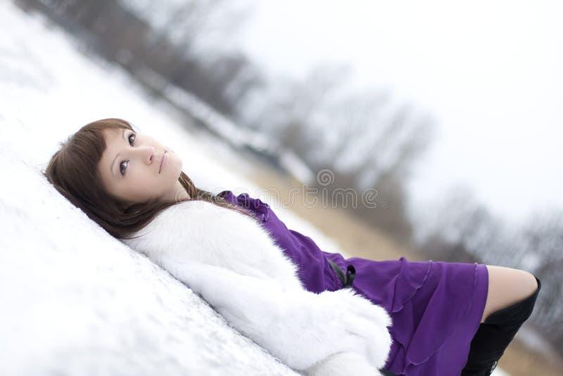 Muchacha que miente en la nieve en alineada imagen de archivo libre de regalías