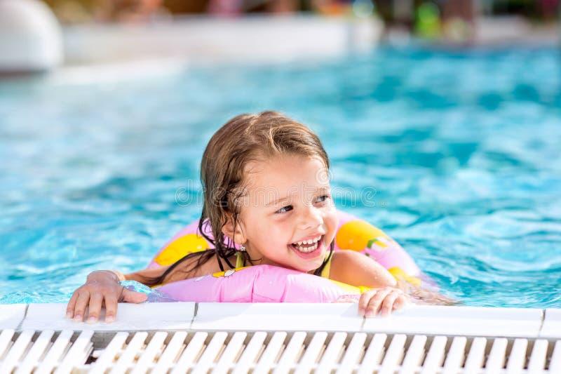 Muchacha que miente en piscina Calor y agua del verano fotografía de archivo