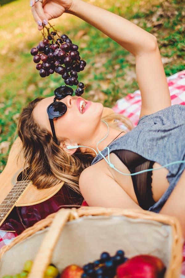 Muchacha que miente en una guitarra y que come las uvas en comida campestre fotos de archivo libres de regalías