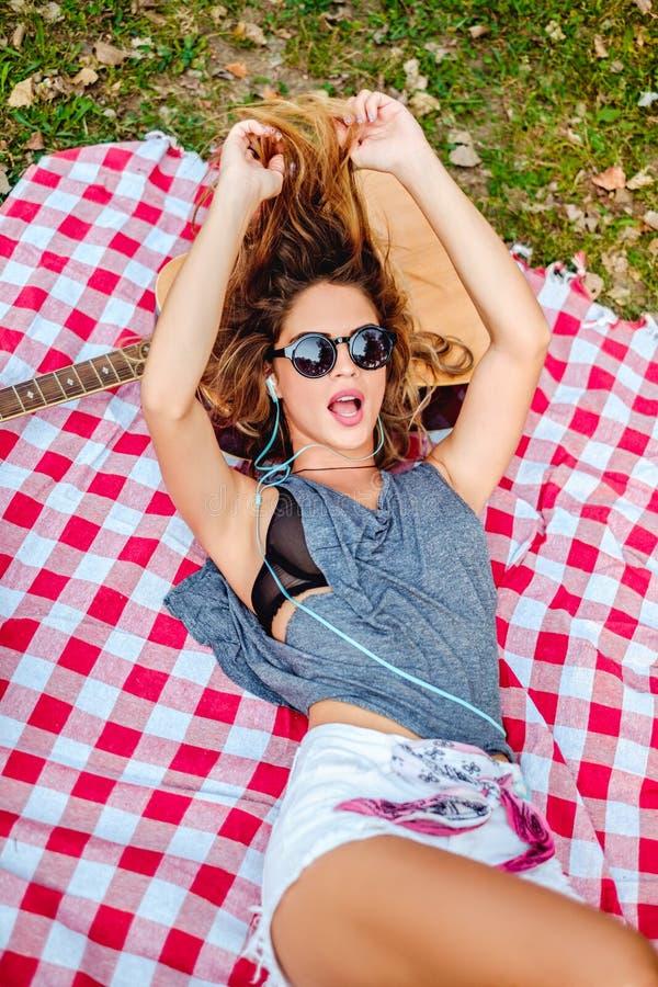 Muchacha que miente en una manta en un parque y que canta imagen de archivo