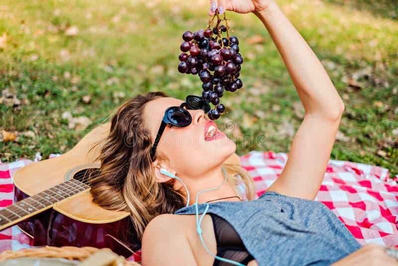 Muchacha que miente y que come las uvas en el parque imagenes de archivo