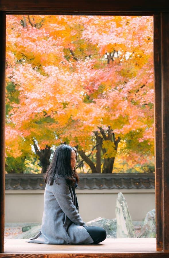 Muchacha que mira árboles de arce rojo en el templo japonés, Kyotogirl que goza de follaje del otoño en el templo japonés, Kyoto fotografía de archivo libre de regalías