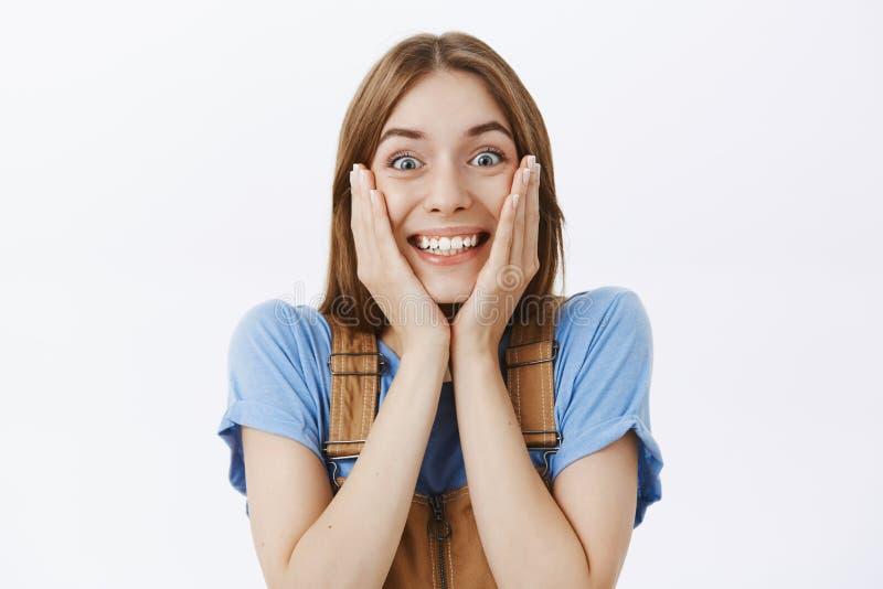 Muchacha que mira con el entusiasmo en la TV que se ve en la pantalla Novia feliz emotiva sorprendente y encantada en marrón foto de archivo libre de regalías