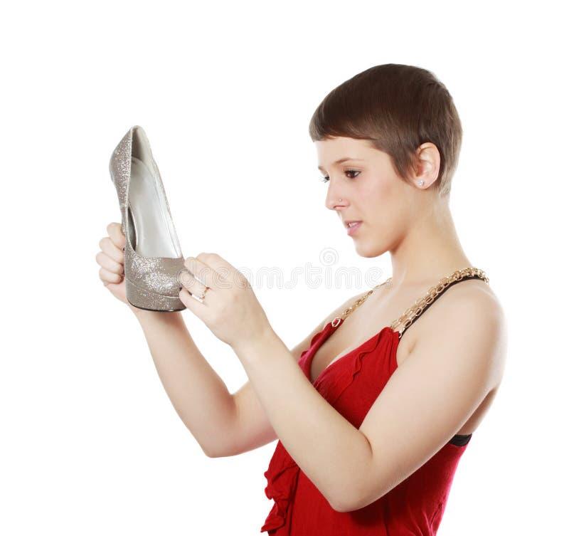 Muchacha que mira de mirada de un zapato imagen de archivo