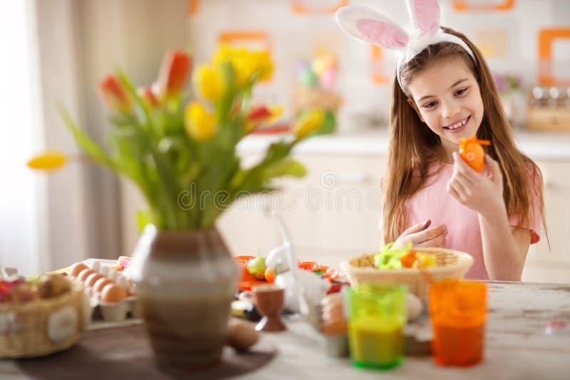 Muchacha que mira el huevo de Pascua pintado foto de archivo