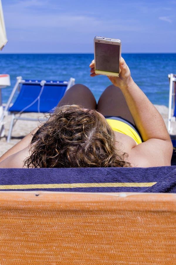 Muchacha que mira el teléfono elegante móvil en una playa con el mar en el fondo para el concepto de la relajación y de la comuni fotos de archivo libres de regalías