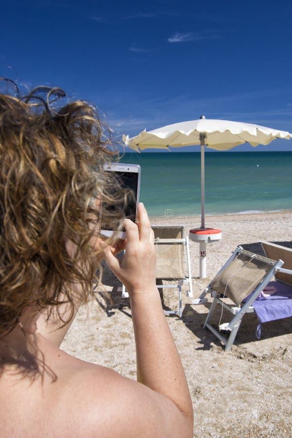 Muchacha que mira el teléfono elegante móvil en una playa con el mar en el fondo para el concepto de la relajación y de la comuni imágenes de archivo libres de regalías