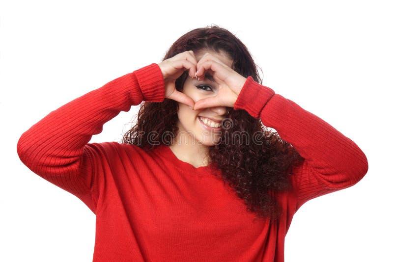 Muchacha que mira a escondidas a través de muestra de la mano de la forma del corazón imagenes de archivo