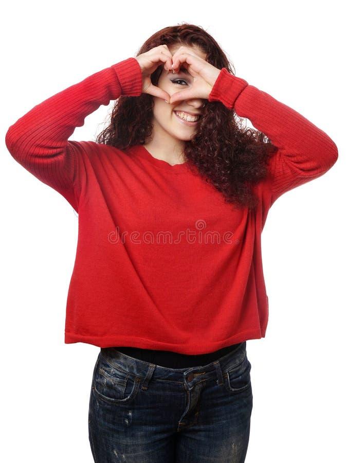 Muchacha que mira a escondidas a través de muestra de la mano de la forma del corazón fotos de archivo libres de regalías