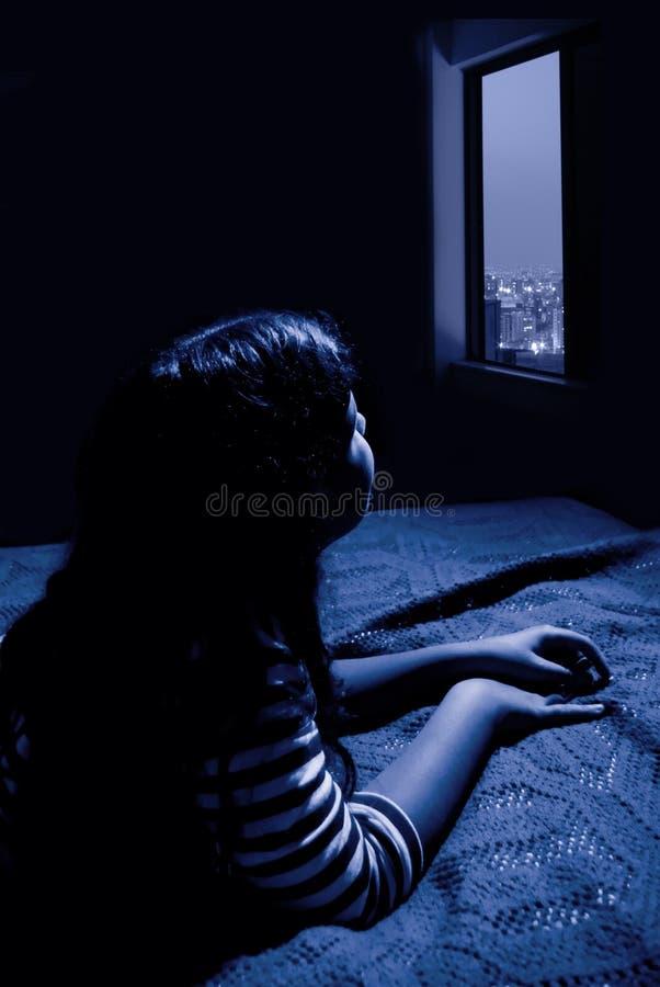 Muchacha que mira hacia fuera la ventana fotografía de archivo libre de regalías