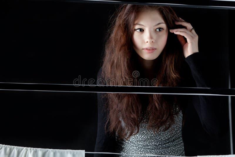 Muchacha que mira hacia fuera la ventana con las cortinas blancas fotografía de archivo