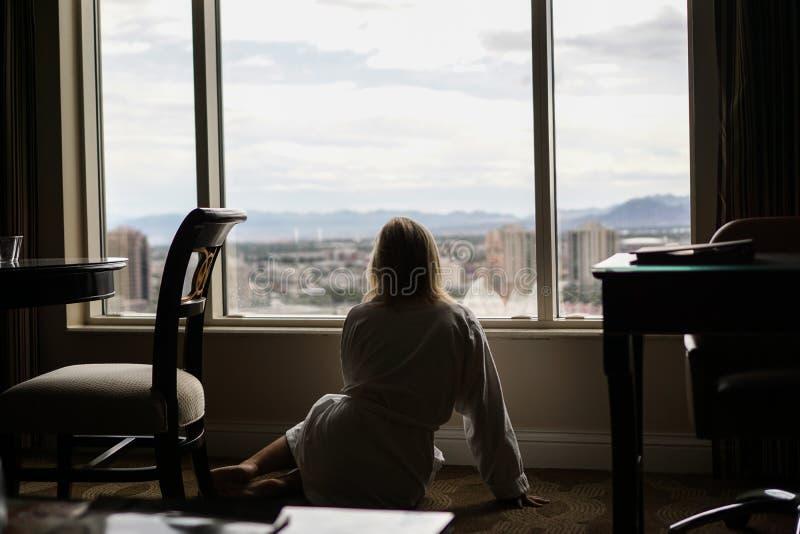 Muchacha que mira hacia fuera la ventana del hotel que se sienta en el piso imagenes de archivo