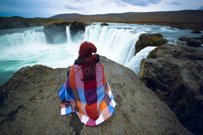 Muchacha que mira la cascada de Godafoss, Islandia imagenes de archivo