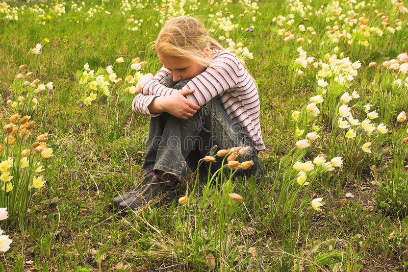 Muchacha que mira la flor del resorte fotos de archivo