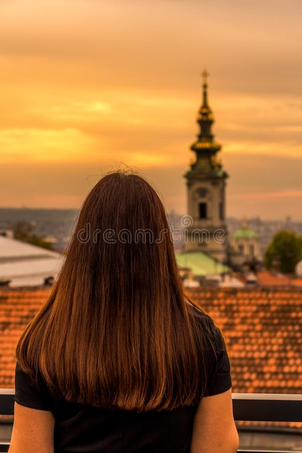 Muchacha que mira la iglesia de Saborna la puesta del sol en Belgrado foto de archivo