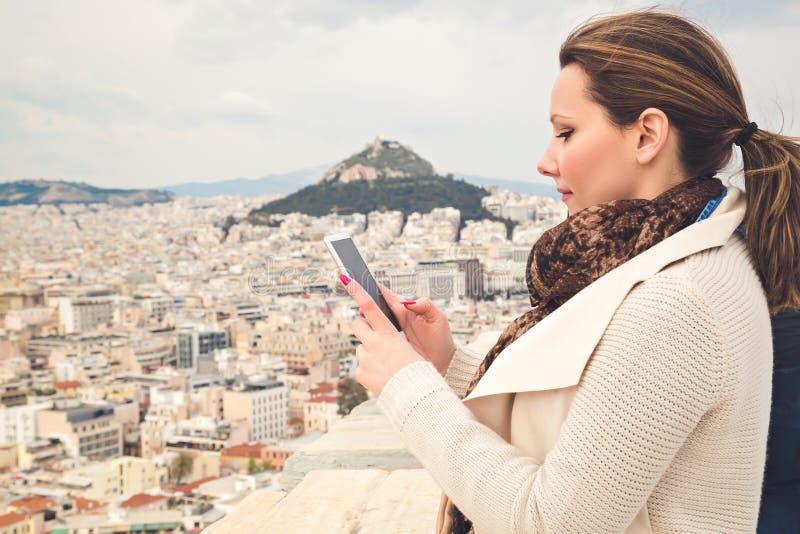 Muchacha que mira la imagen de una ciudad en su teléfono móvil imágenes de archivo libres de regalías
