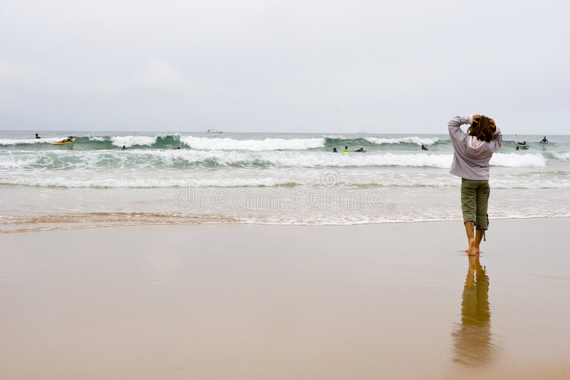 Muchacha que mira a personas que practica surf fotografía de archivo