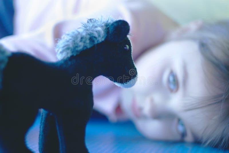 Muchacha que mira su caballo relleno del juguete imagen de archivo libre de regalías