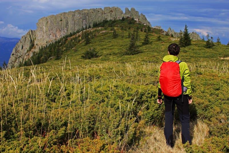 Muchacha que mira una cresta de montaña enorme en la distancia foto de archivo