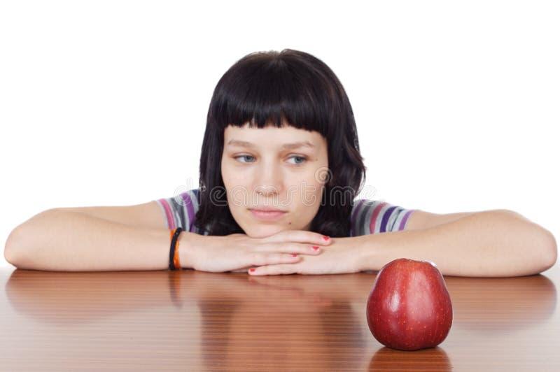 Muchacha que mira una manzana roja fotografía de archivo