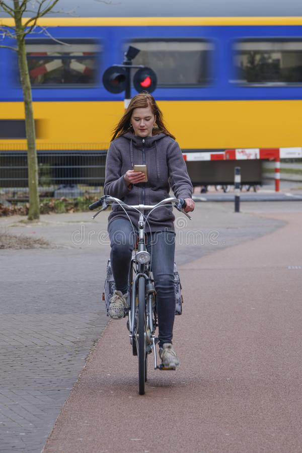 Muchacha que monta una bici y miradas en su smartphone, peligro imagenes de archivo