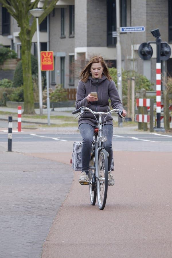 Muchacha que monta una bici y miradas en su smartphone, peligro fotos de archivo libres de regalías
