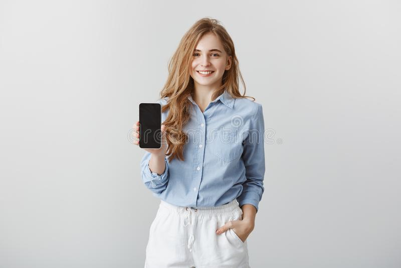 Muchacha que muestra el nuevo teléfono al colega Retrato del blogger europeo de amistoso-mirada encantador de la moda en azul for foto de archivo libre de regalías