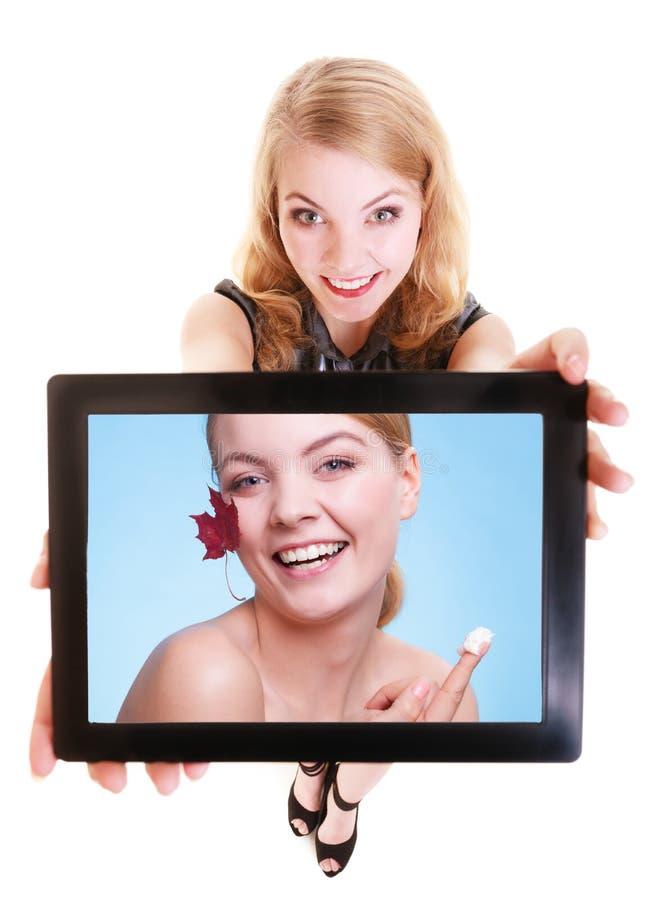 Muchacha que muestra a la mujer con crema en la tableta. Cuidado de piel fotos de archivo libres de regalías