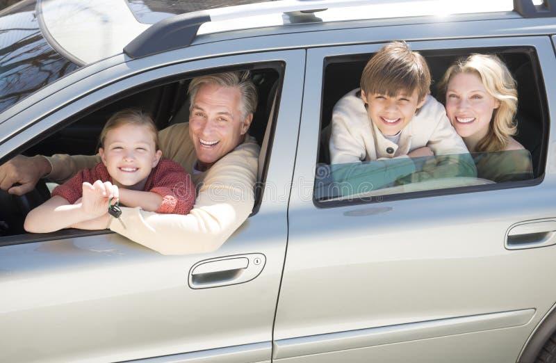 Muchacha que muestra llaves del coche mientras que se sienta con la familia en coche fotografía de archivo libre de regalías