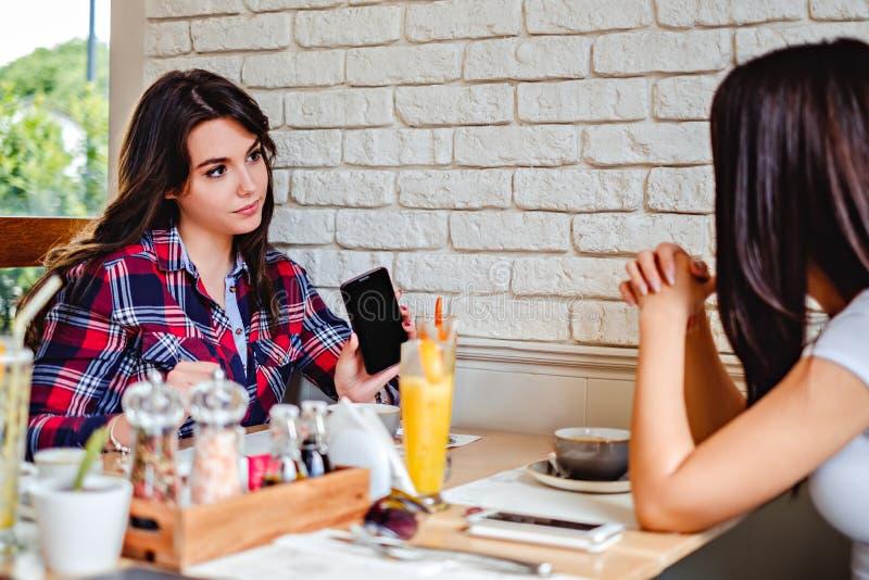 Muchacha que muestra su teléfono móvil en el restaurante fotografía de archivo