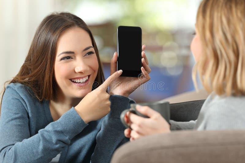Muchacha que muestra una pantalla en blanco del teléfono a un amigo en casa imágenes de archivo libres de regalías