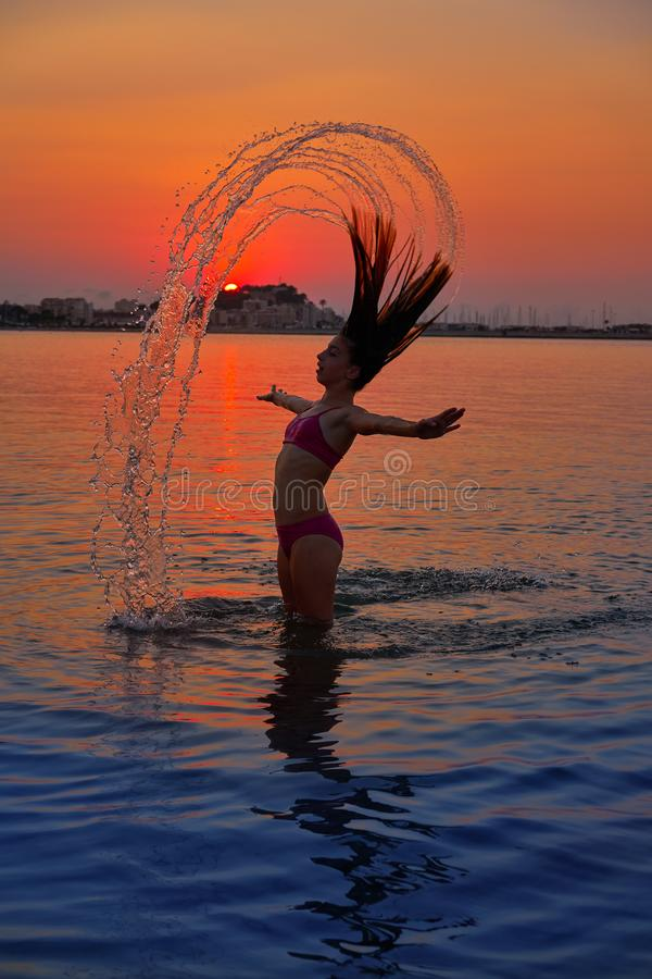 Muchacha que mueve de un tirón tirón del pelo en la playa de la puesta del sol foto de archivo libre de regalías