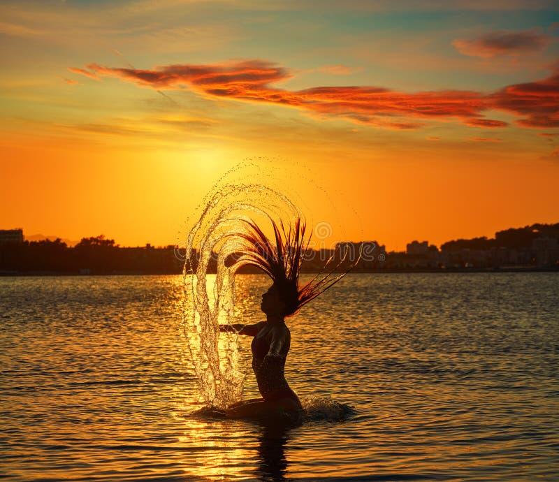Muchacha que mueve de un tirón tirón del pelo en la playa de la puesta del sol fotos de archivo libres de regalías