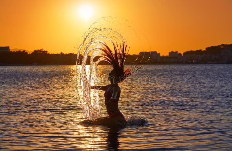 Muchacha que mueve de un tirón tirón del pelo en la playa de la puesta del sol imagen de archivo