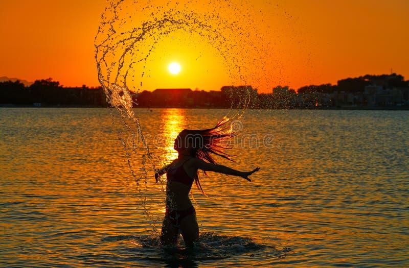 Muchacha que mueve de un tirón tirón del pelo en la playa de la puesta del sol imagenes de archivo