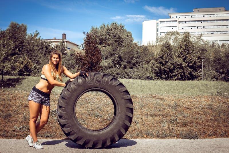 Muchacha que mueve de un tirón el neumático durante ejercicio imagenes de archivo