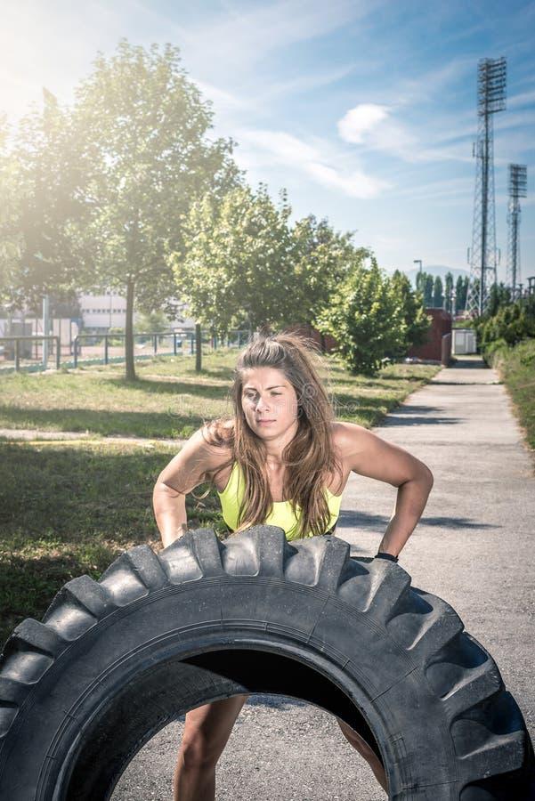 Muchacha que mueve de un tirón el neumático durante ejercicio fotos de archivo