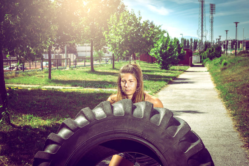 Muchacha que mueve de un tirón el neumático durante ejercicio fotografía de archivo