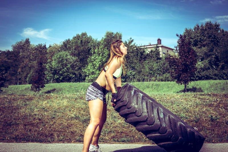 Muchacha que mueve de un tirón el neumático durante ejercicio fotografía de archivo libre de regalías