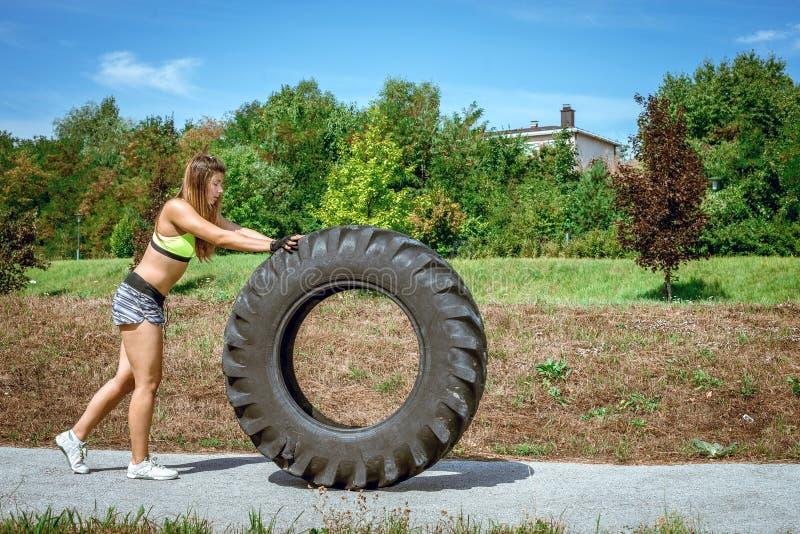 Muchacha que mueve de un tirón el neumático durante ejercicio fotos de archivo libres de regalías