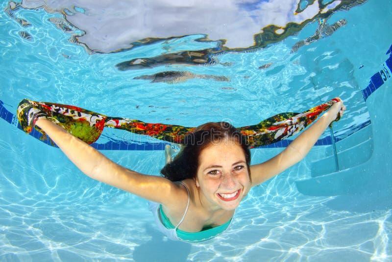 Muchacha que nada bajo el agua con una bufanda imagenes de archivo