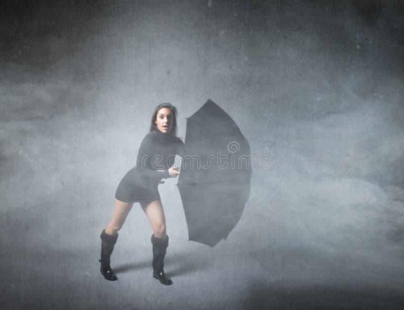 Muchacha que oculta con el paraguas foto de archivo