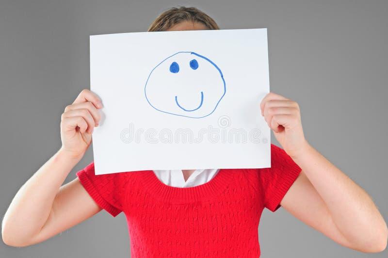 Muchacha que oculta detrás de cara feliz imagen de archivo