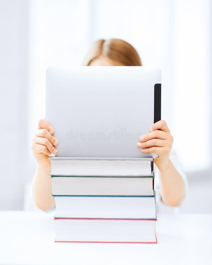 Muchacha que oculta detrás de la PC y de los libros de la tableta en la escuela fotos de archivo libres de regalías