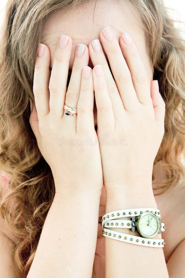 Muchacha que oculta detrás de sus manos fotos de archivo