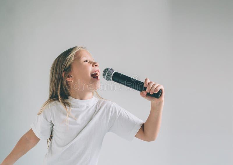 Muchacha que oscila hacia fuera Imagen de un niño que canta al micrófono, aislada en luz Retrato emocional de un niño atractivo imagen de archivo