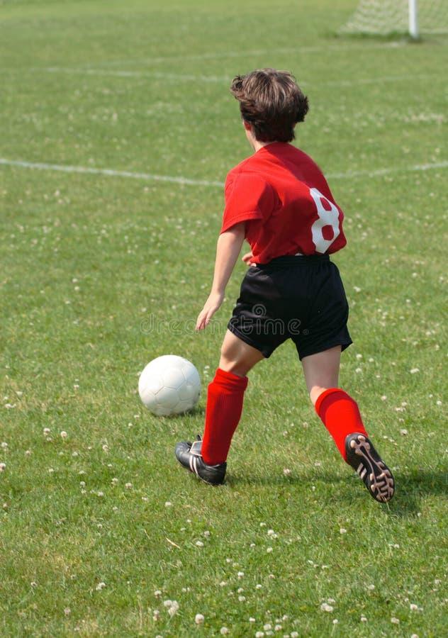 Muchacha que persigue el balón de fútbol fotos de archivo
