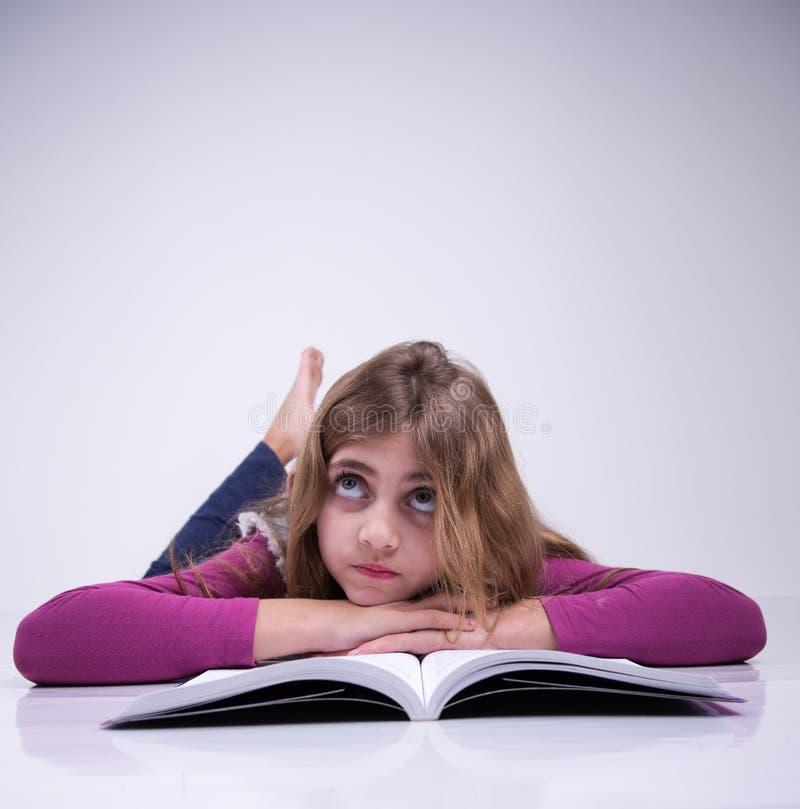 Muchacha que piensa en lo que ella estudió imagenes de archivo