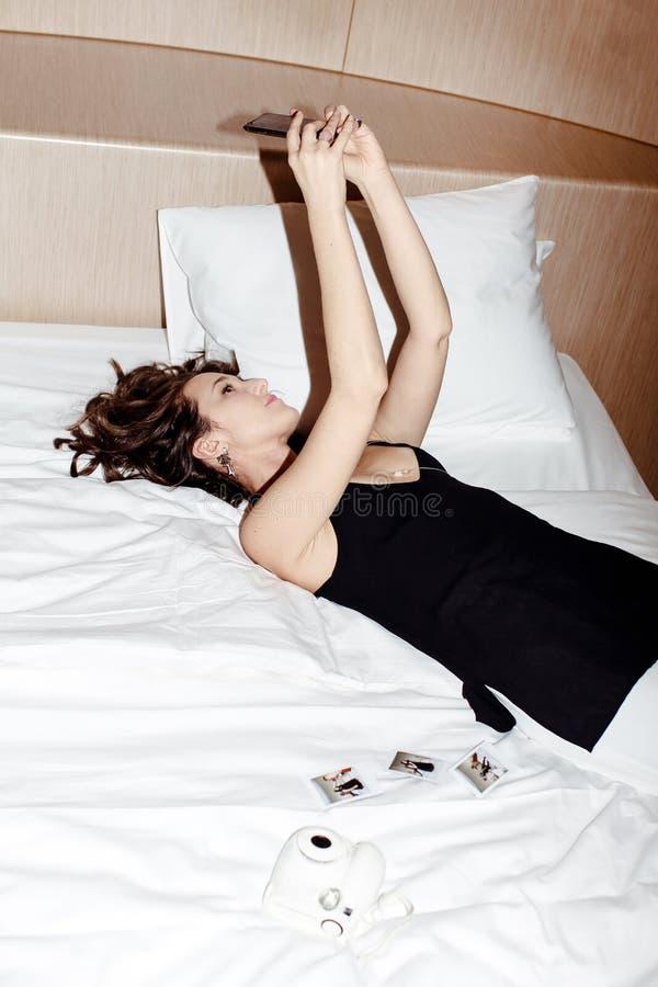 Muchacha que pone en cama y que hace el selfie en su teléfono fotos de archivo libres de regalías